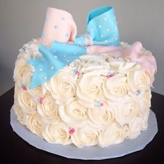 White rosette gender reveal cake with pink and blue fondant bow