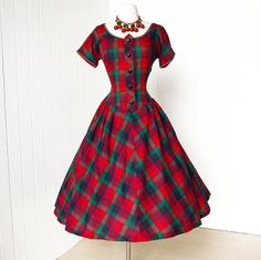 Wow wow wow! Tis the season to be jolly! A classic tartan plaid pattern is fashioned into this lovely 1950s dress with a tab trim at the neckline. Gorgeous! #1950s #dress #plaid