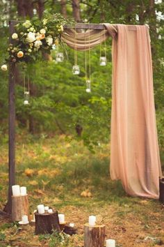 fabric draped wedding arch with floral and hanging manson jar lights