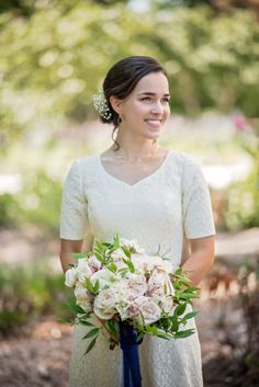 Beautiful bride with white roses and vintage dress at summer barn wedding in Maryland
