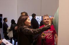 Heashin Kwak, Hanmi Gallery Director adding coins to Sungfeel Yun's art work