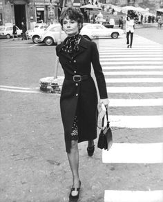 Signora Audrey Hepburn Dotti photographed by Lino Nanni inRome (Italy), in April 1972. Audrey was wearing: Coat:Valentino(of wool, navy blue, of his couture collection for the Autumn/Winter 1970/71). Dress(inside)with a matching scarf:Valentino(of silk, black with details in white,of his couture collection for the Spring/Summer of 1972). Pearl necklace:Bvlgari. Belt:Céline(of leather, navy blue, of the collection for the Autumn/Winter 1969/70). Bag:Gucci. Shoes:Bruno Magli.