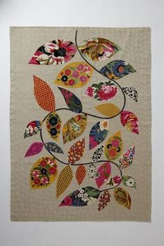 I want to take the girls' cute baby clothes and cut leaf shapes and applique a wall hanging like this to always remember their cute baby clothes....