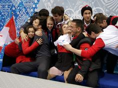 Meagan Duhamel and Eric Radford of Canada hug teammates and coach Richard Gauthier (L) after competing in the Figure Skating Pairs Short Pro...
