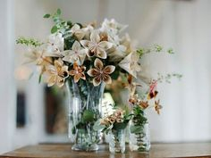 There are some stunning paper flower creations out there and I love this idea of combining the paper flowers with some living green foliage – here they've used some eucalyptus, but I think grasses would also look beautiful.  I also like the idea of creating your wedding reception table centrepieces with a mixture of filled tall vases and then tiny ones around the base.  It's a bit more interesting than just one vase in the middle, and the tiny paper flowers are so sweet.