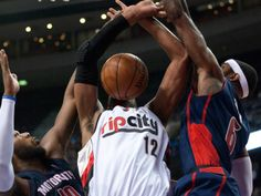 Blazers forward LaMarcus Aldridge (12) tries to corral a rebound between Pistons forwards Josh Smith (6) and Greg Monroe (10)...