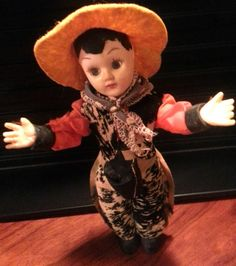 "This has to be the sharpest dressed cowboy doll  I've ever seen! Circa 1950's, he wears a wonderful large rimmed yellow felt cowboy hat. Shiny orange long sleeve shirt with black vinyl (looks like leather) cuffs under a ""zebra hair on hide"" vest with matching un-fringed chaps. The bandanna tied around his neck is dark blue with white polka-dots. He is 7-1/4"" tall plastic doll with sleepy eyes."