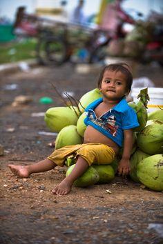 Child will coconuts at the market, Phnom Penh, Cambodia
