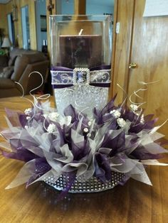 Wedding center peice with plum and silver organza ribbon,  bling floral picks, and silver twisted floral decor. Please visit www.facebook.com/cornerstonedesigns for more items or contact info if you want to order.