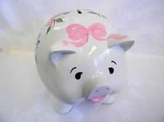 Requested by a customer this hand painted piggy bank has beautiful roses and buds in shades of pink over vines and leaves in medium green and light green. A dark pink butterfly is on the back with white and black details with a ring of roses in shades of pink around the tail and a adorable pink bow on the forehead.  A wonderful compliment from a satisfied customer: I absolutely LOVE Oaklees piggy bank!!! Its beautiful!!! Thank you so much!!! Also, thank you for the quick delivery and for…
