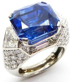 Single stone sapphire and diamond cluster ring by Cartier, Paris, the cut-corner rectangular Ceylon sapphire, 17.55ct,  claw set in landscape and flanked by collet set kite shaped diamonds, raised in high pavй diamond set mount of faceted design, serial number 9543, mounted in platinum. S.J. Philips.