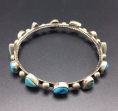 VINTAGE NAVAJO BRACELET  DESCRIPTION: This fabulous bangle features 12 cabochons of turquoise, punctuated with applied raindrops, on a heavy gauge sterling silver bangle. This bracelet will be a cherished addition to your collection of fine vintage Native American jewelry.  MEASUREMENTS: Interior of the bangle measures 7 1/2  Measures 2 1/2 straight across the widest part of the bangle (from wrist bone to wrist bone)   WEIGHT: 28.6 grams SIGNED: CHIMNEY, for Chimney Butte (Eric Chase…