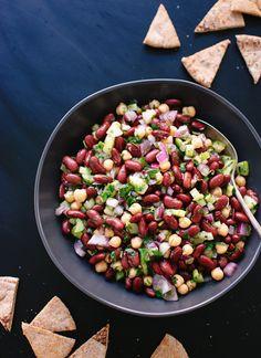 Ingredientes – 400 g de frijoles rojos, enjuagados y escurridos – 400 g de garbanzos, enjuagados y escurridos (también pueden ser cocidos) – 1 cebolla roja pequeña, cortada en cubitos – 2 tallos de apio, cortado por la mitad y picado – 1 tomate maduro rojo y picado (omitir si no se puede encontrar un gran tomate) – 1 pepino mediano, pelado, sin semillas y cortado en cubitos – 3/4 de taza de perejil fresco picado – 2 cucharadas de eneldo fresco picado o menta – 1/4 de taza de aceite de oliva…