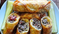 Bacon Cheeseburger Eggrolls.... What a great idea, and super easy to make! Simply fry your ground beef with seasoning and onions if you wish & cook some bacon. Than add a spoonful to an egg roll wrap, along with some bacon and cheese. Roll it up, seal it and either deep fry or bake. Set out your favorite condiments as dunkers and you're good to go. Yum!