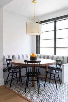 dining room 156007574578698384 - A white drum cage pendant hangs over an oval wood dining table placed on white and black mosaic floor tiles and seating two black Windsor dining chairs facing a white l-shaped dining banquette. Source by knatschinats Room Tiles Design, Dining Room Design, Windsor Dining Chairs, Dining Room Chairs, Dining Decor, Round Dinning Room Table, Couch Dining Table, Dining Booth, Round Dining Table Modern