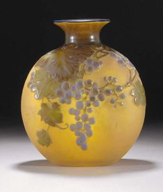 A GALLÉ MOULD-BLOWN GLASS VASE - the internally yellow and amethyst frosted glass overlaid in shades of green and purple, mould-blown and etched with grape clusters and trailing vines, cameo mark Gallé -- 28cm. high