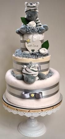 A 3 tier nappy cake in neutral colours featuring a Zooma Zebra soft toy and ring ratt…