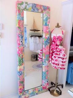 """This mirror appears to be in a Lilly shop but could definitely be recreated by building a wood frame around a full length mirror and covering it in fabric.  I would love to have one covered in """"Lilly State of Mind Patch."""""""