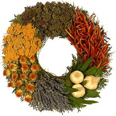 A spice and herb cabinet for the wall! Beautiful wreath collection of dried oregano, chilies, orange safflower, English lavender, golden yarrow, bay leaves and crowning garlic heads.