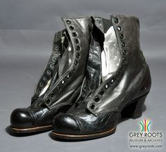 """A pair of ladies', black, high-topped boots made by """"The McPherson Shoe"""". The boots have a stacked heel and a perforated decoration on the toe. The boots are made of two different types of black leather which have slightly different shades. Grey Roots Museum & Archives Collection."""