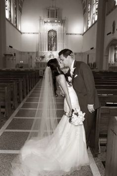 Bride and groom kisses at the church with the altar in the background - black and white - sepia toned picture by George Troup Photography