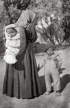 Pomo Indian woman carrying baby in cradleboard. Lakeport, California. 1900-1940.