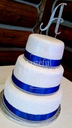 A 3 tier white fondant wedding cake, encrusted with shimmering dust, hand piped cornelli lace for the bottom tier, accented with ribbon, diamond banding and crystal monogram.  Seward, Nebraska. Cake to Die For!