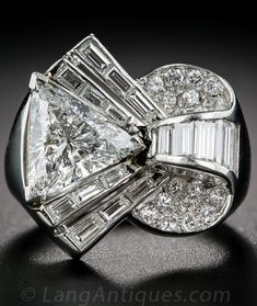 Deco/Retro Platinum and Diamond Cocktail Ring, centering on a faceted triangle, or trilliant, cut diamond weighing carats. The artfully sculpted, multi-dimensional mounting combines baguette and round diamonds for a brilliant effect. Bijoux Art Deco, Art Deco Jewelry, Fine Jewelry, Jewelry Design, Cheap Jewelry, Vintage Diamond Rings, Diamond Jewelry, Jewelry Rings, Jewelry Accessories