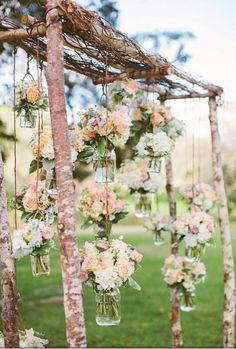 Mason jars full of fresh flowers dangling on your wedding arch! #MasonJarWeddingIdeas