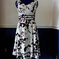 Cream and chocolate tea dress Chocolate brown ribbon accents slightly under the bust gives attention to the waistline. Beautiful on, very feminine. Hidden back zipper, book and eye closure. Fully lined. 100% polyester Dry clean Dress Barn Dresses