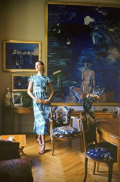 French model Jacky Mazel is seen wearing Claire McCardell's cocktail dress standing in the salon of Raoul Dufy, where a collection of his paintings hang, photo by Mark Shaw, 1955