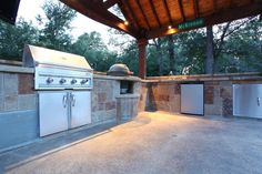 Very spacious outdoor kitchen featuring stainless appliances: BBQ, refrigerator, additional storage with stainless doors and a built in spot for the green egg! By Outdoor Signature in Argyle, TX