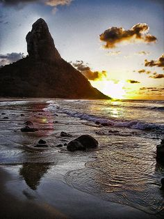 Praia da Conceição at sunset. Morro do Pico is in the foreground. It is in Fernando de Noronha, a natural park off the coast of Brazil.