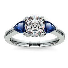Trillion Sapphire Gemstone Engagement Ring in Platinum Two perfectly matched trillion cut sapphire gemstones are prong set in this platinum gemstone engagement ring setting, accenting your choice of center diamond (not included). Proudly made in the USA.