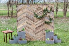 cinder blocks stacked & planted with greenery-embroidery hoops w more greenery on rustic fence boards Pallet Backdrop, Diy Pallet Wall, Diy Backdrop, Photo Booth Backdrop, Ceremony Backdrop, Christmas Stage Design, Christmas Photo Booth, Backdrops For Parties, Wedding Backdrops