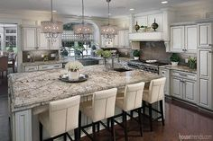 A quartet of barstools stands at attention at the granite-topped island, while a group of lights overhead adds a little glamour to this kitchen. #housetrends