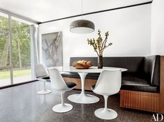 In the breakfast area, a Jasper Morrison pendant light for Flos hangs above a table and chairs by Eero Saarinen for Knoll and a Brad Dunning–designed banquette cushioned in an Edelman leather; the artwork is by Jonah Freeman and Justin Lowe | archdigest.com