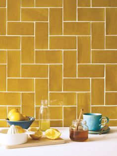 While these Carnival Oro Tiles from Fired Earth would look lovely as part of an otherwise white scheme, we also love the idea of choosing a complementary botanical wallpaper. #metrotiles #yellow #mustard #kitchen #kitchentiles #realhomes