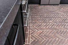 In deze keuken plaatsten we een gemeleerde Brickthinsvloer in visgraatmotief. De kleuren sluiten goed aan bij de zwarte keuken. Ook de vloer van het toilet hebben we in dezelfde stijl geleverd.