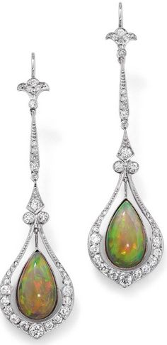 A pair of opal and diamond ear pendants. Each designed as a central millegrain-set pear-shaped opal suspended within an articulated drop-shaped frame set with circular-cut diamonds to a tapered and foliate similarly cut diamond surmount, length 6.5 cm, wire earfittings. Via Phillips.