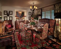 Tartan plaid, leather, and toile coordinated with the vintage fabric on the chairs create a setting for a bountiful dining room.