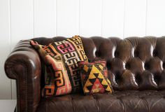 brown leather chesterfield sofa + ikat pillows