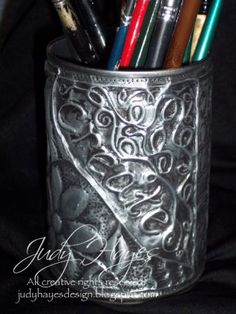 a pencil holder made from a tin can covered with embossed craft foil, all original doodle design