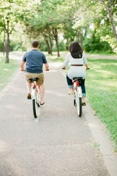 Couple Riding Red Bikes in Park
