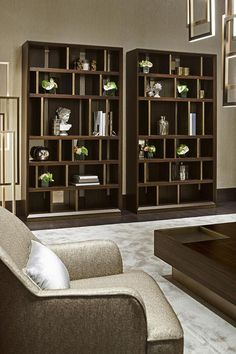 Living room with bookshelves Magritte, by Oasis. The bookshelf, featuring an uneven distribution of the spaces, is composed by a single module, joinable, with dividers in antique gold. A piece of furniture which finds its rightful place in the living areas of every style, from classic to contemporary.