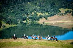 Horseback riders in front of the lake at Alisal Guest Ranch and Resort in the Santa Ynez Valley, California