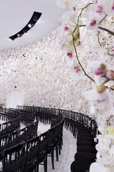 orchid-covered wall + black frame chairs