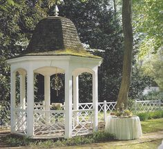 Nelson-Galt Gazebo in Colonial Williamsburg, Virginia - The gazebo with its moss covered roof and Chippendale railing is decorated for a party to greet the arrival of spring. A double hoop covered with fresh flowers and boxwood hangs above a bowl of May wine that is garlanded with a sweet woodruff and strawberry wreath.