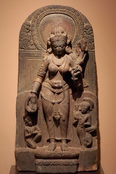 "Goddess Tara, late 9th century, India: Bihar, schist.  The Buddhist deity Tara is the goddess of compassion and action, who aids devotees in overcoming personal difficulties. The inscription inside her halo is the Buddhist creed, which reads ""[Buddha] has revealed the cause of those phenomena which spring from a cause and also [the means of] their cessation. So says the Great Monk."" Tara, holding a lotus, is considered the female aspect of the Universe, and in some aspects as a Mother…"