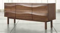 With its unique, flowing sculptural facade, the Apex sideboard transcends decades, blending easily with mid-century decor as well as more contemporary styles. Bringing dimension to the grain of solid American walnut and veneer, carved waves travel seamlessly over the entire length of this stunning sideboard, cleverly concealing two doors and three drawers.